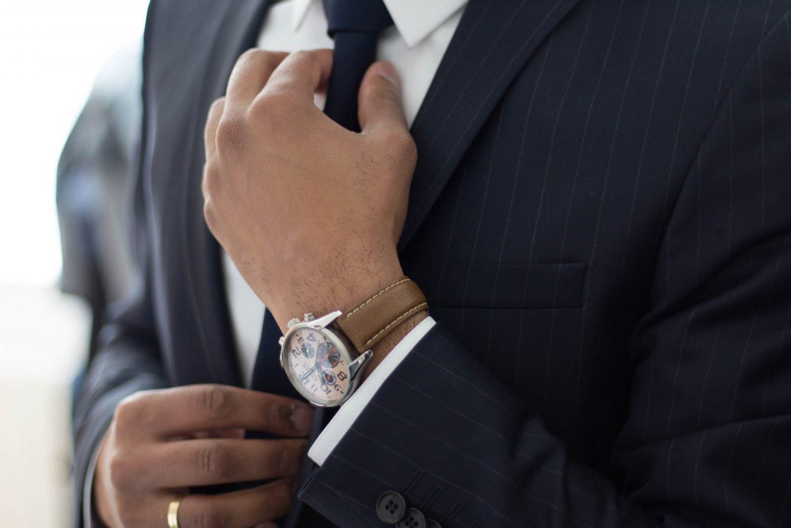 Successful businessman adjusting his tie